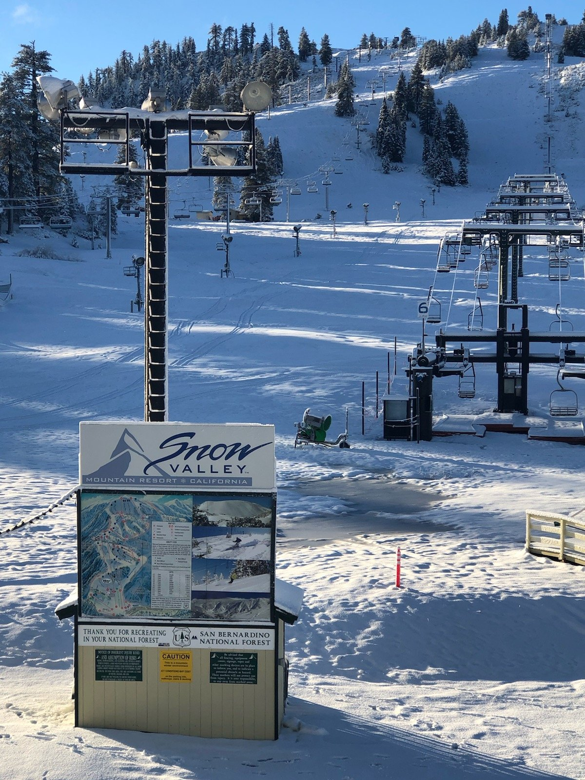 Large Snow Valley terrain map stands in front of ski lift on a clear day
