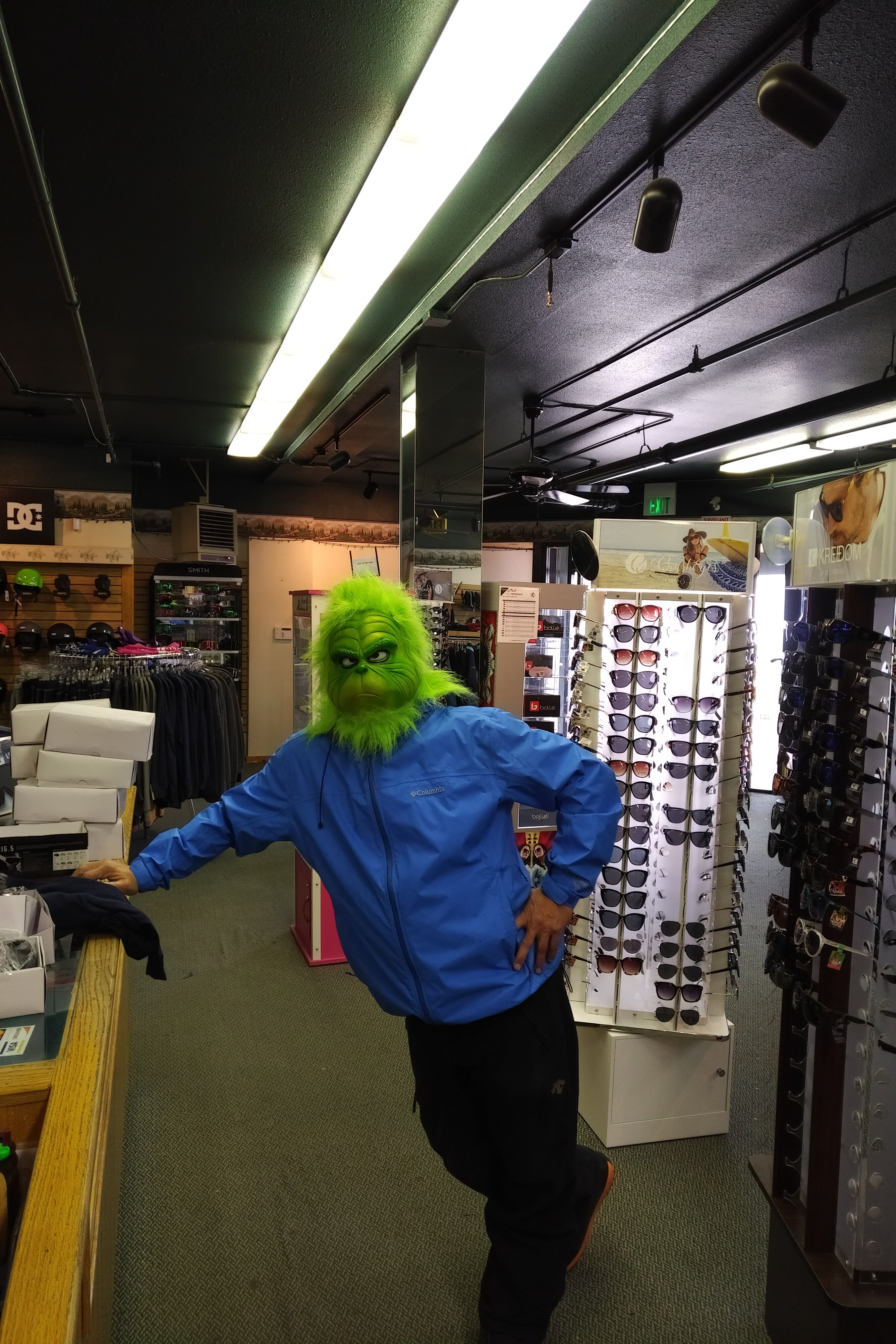 Man stands in Snow Valley gift shop wearing Grinch mask