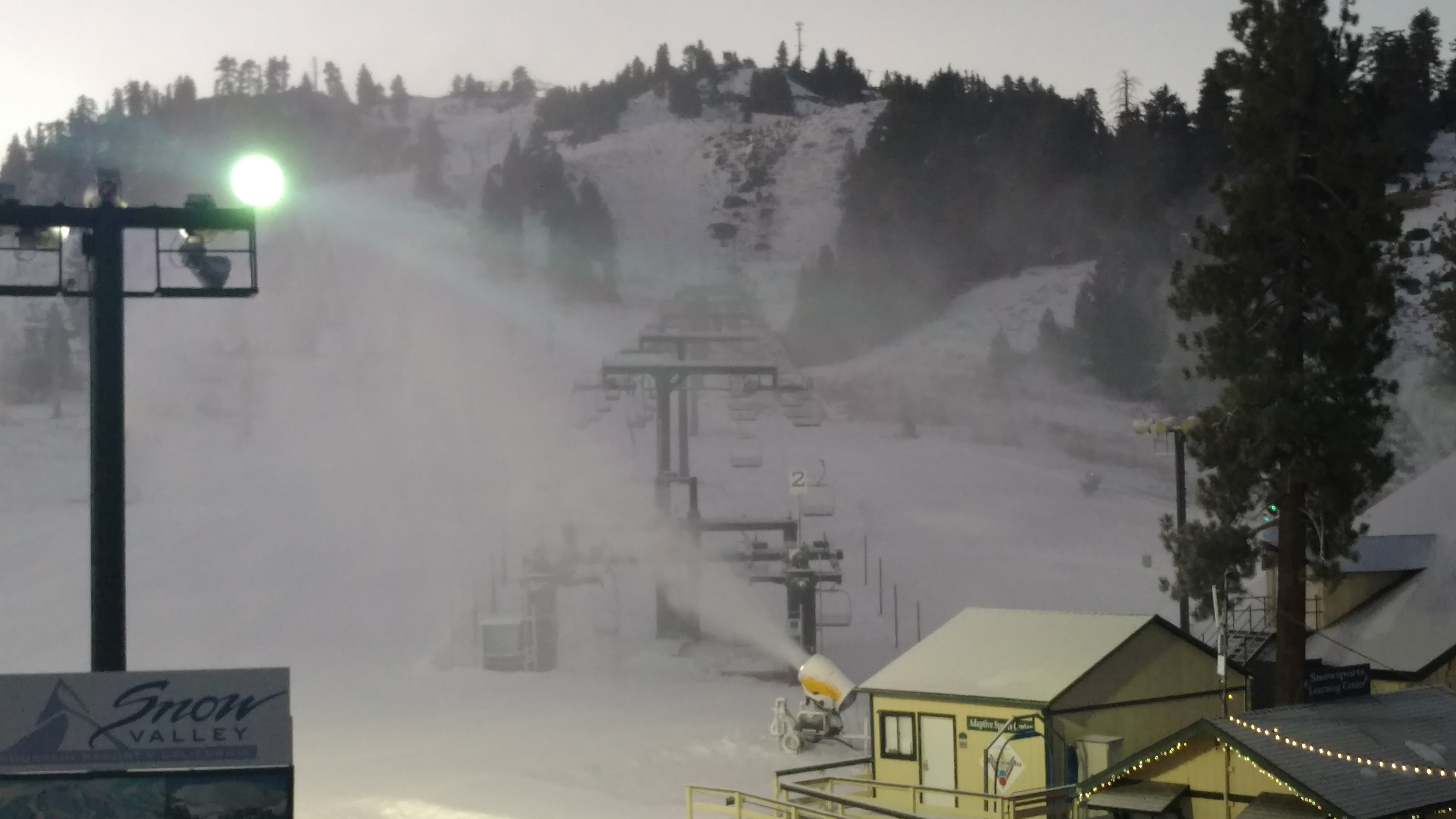 Snow making machines in action during sunset