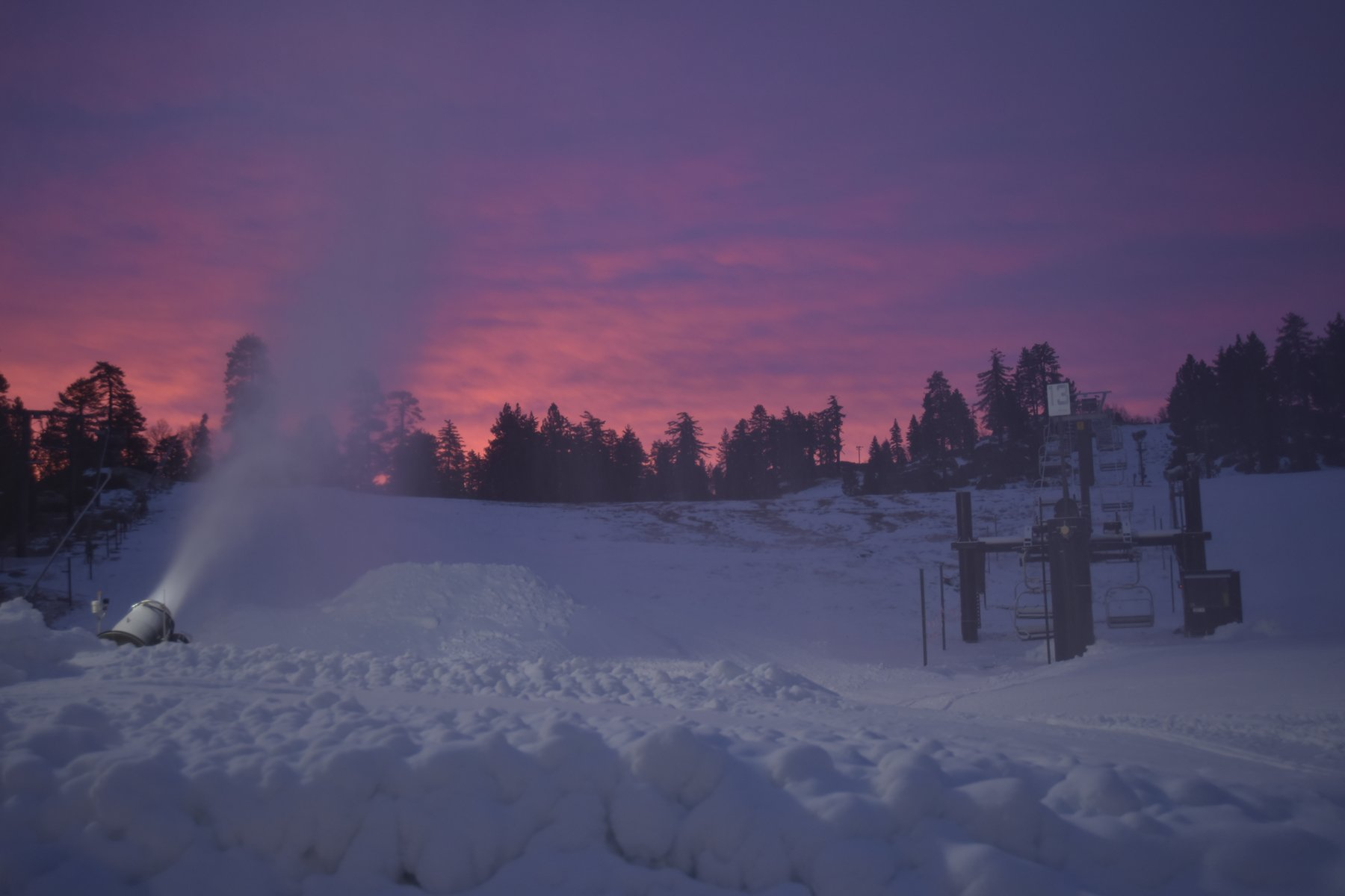 Snow making machine blows fresh snow into air in front of a brilliant pink sunset