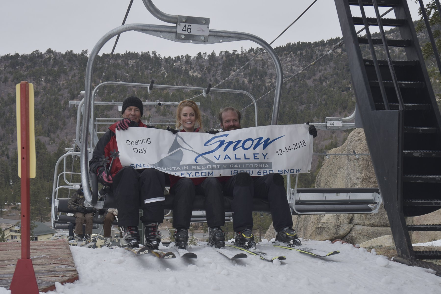 "Three people on Snow Valley lift holding sign that reads ""Opening Day 12-14-2018"""