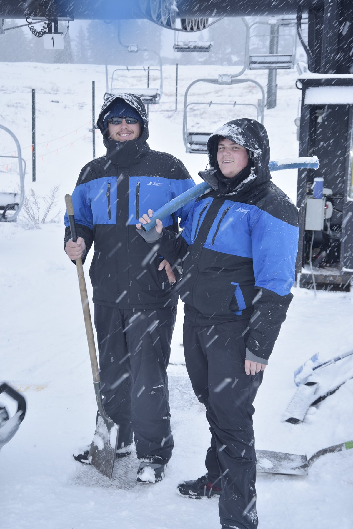 Two Snow Valley employees posing in front of ski lift smiling during snowfall