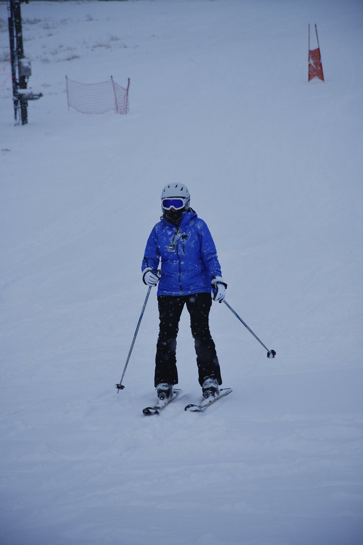Person skiing with helmet, gloves, mask, and snow pants