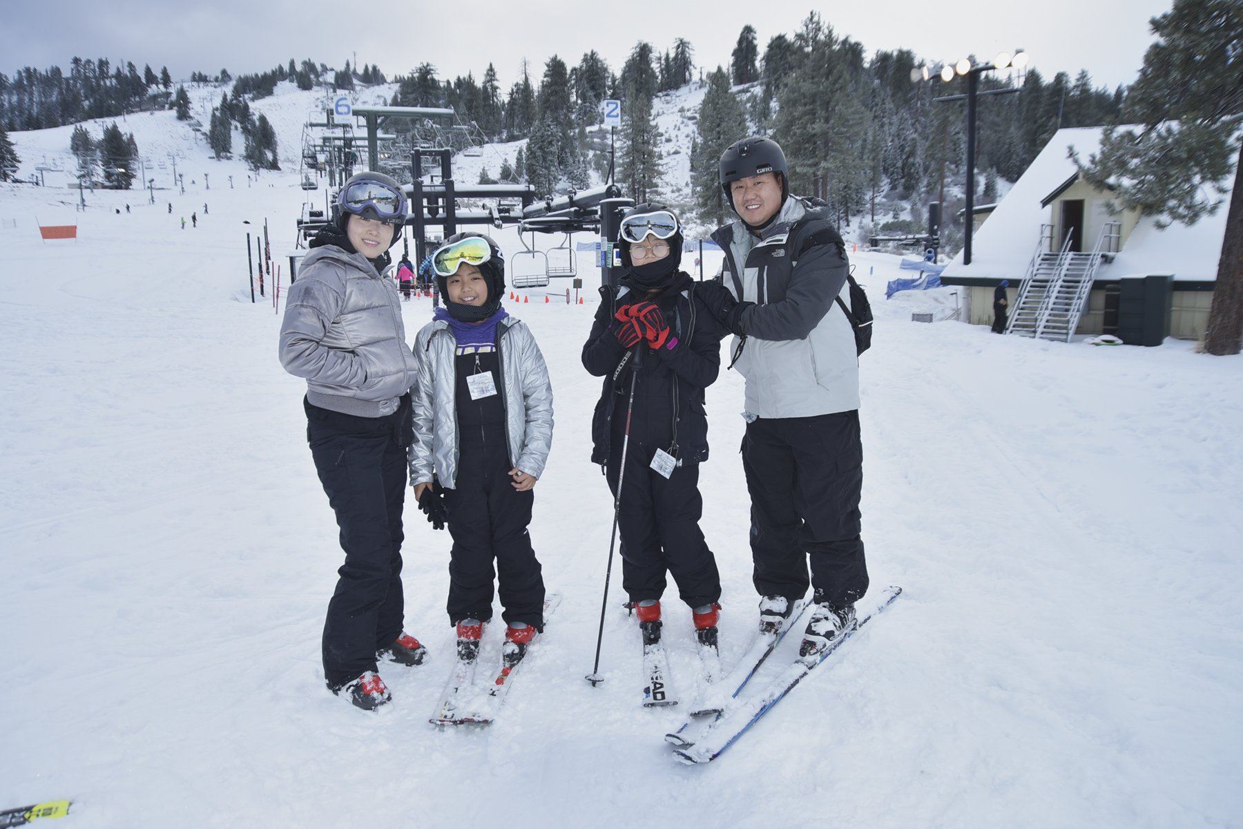 Two parents and two children pose with skis on in front of ski lifts