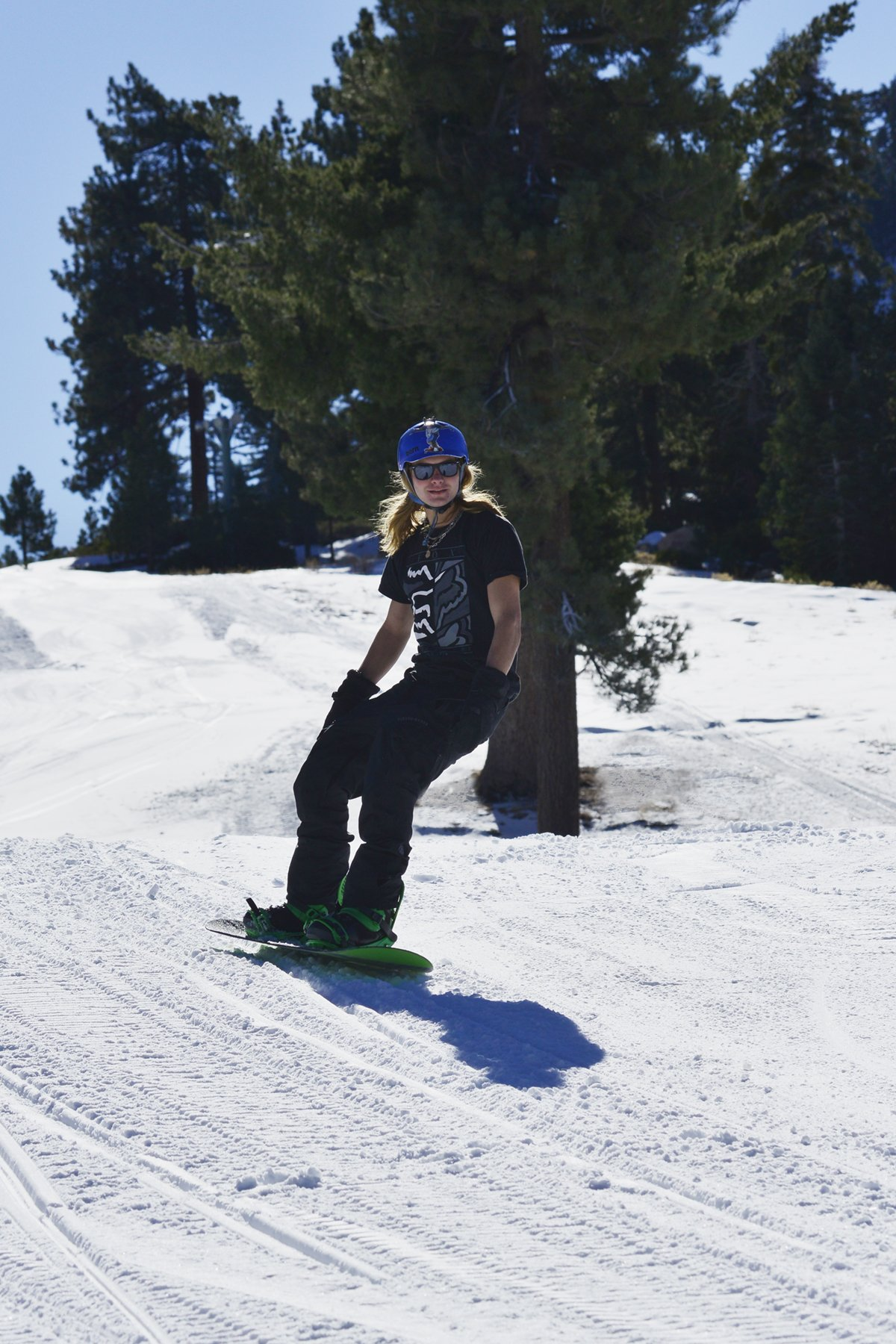 Action shot of snowboard heading dowhill with a black t-shirt on