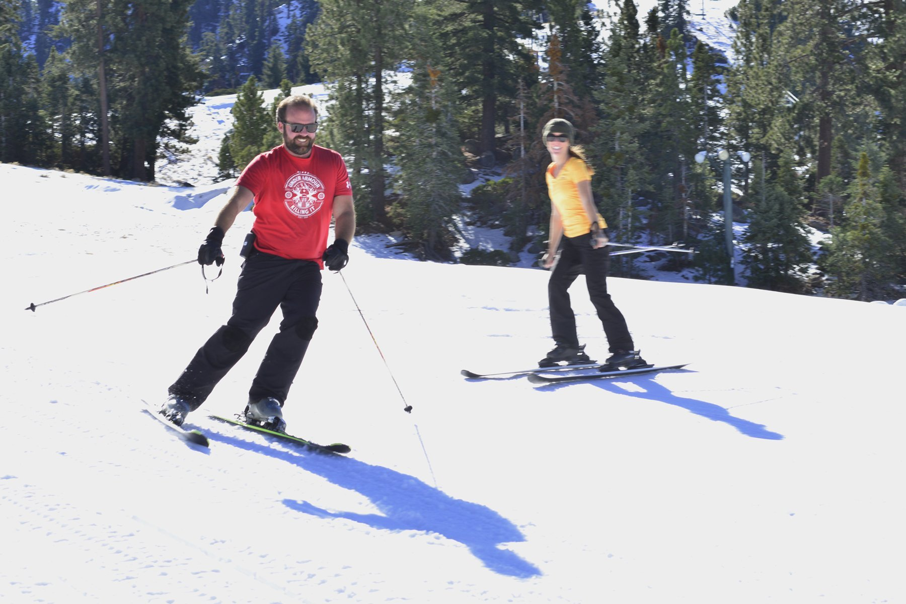 Action shot of couple skiing downhill in t-shirts on a sunny day