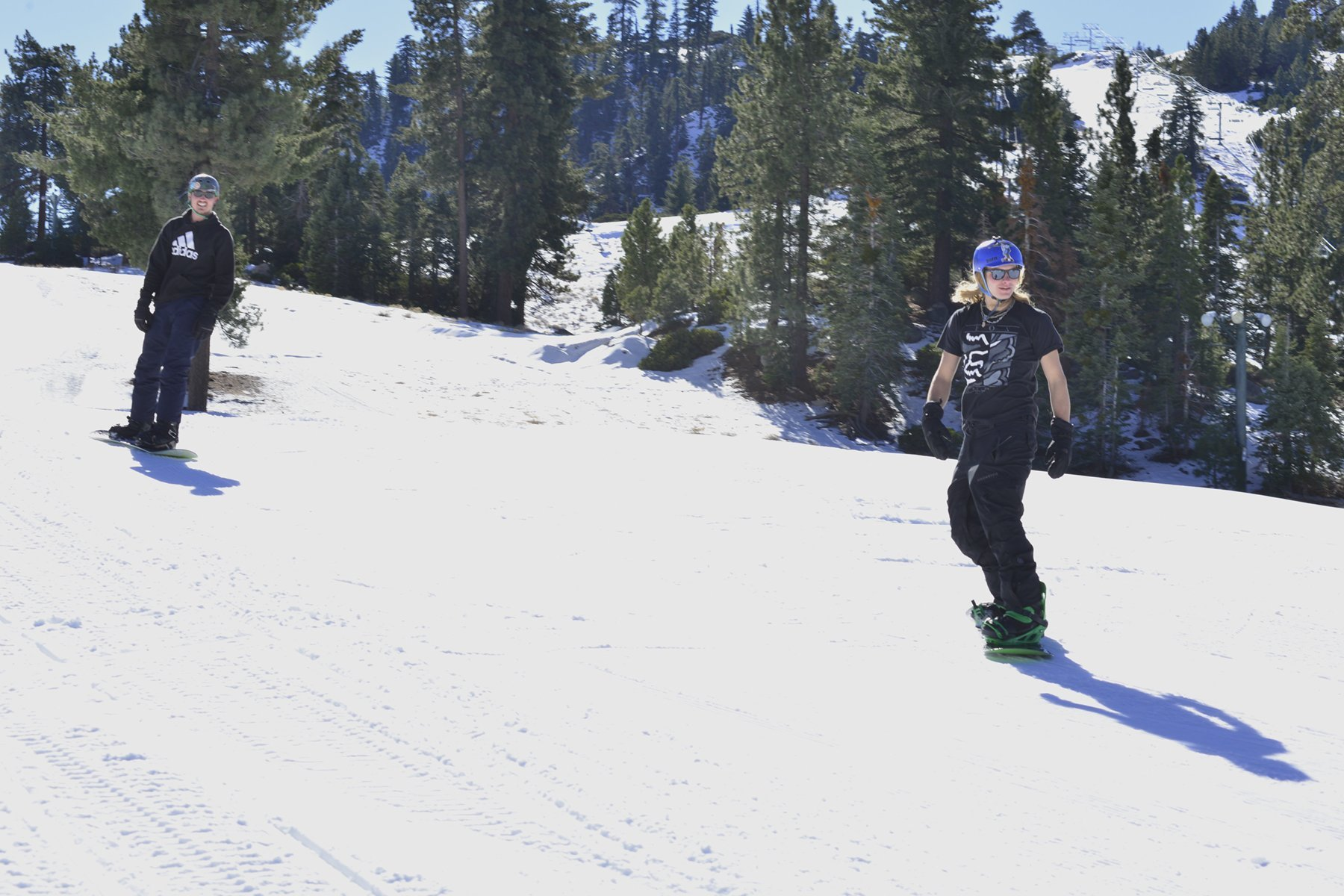 Two smiling snowboarders heading downhill in casual wear