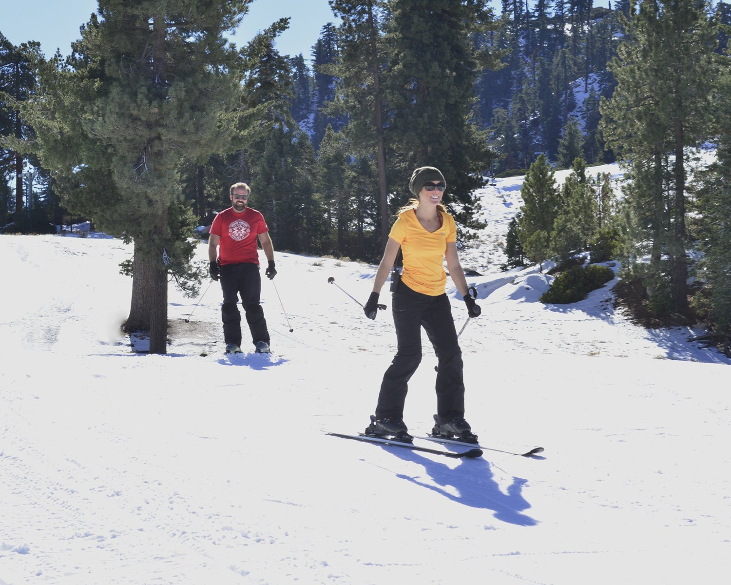 A male & female skiier skiing across gentle slope in t-shirts