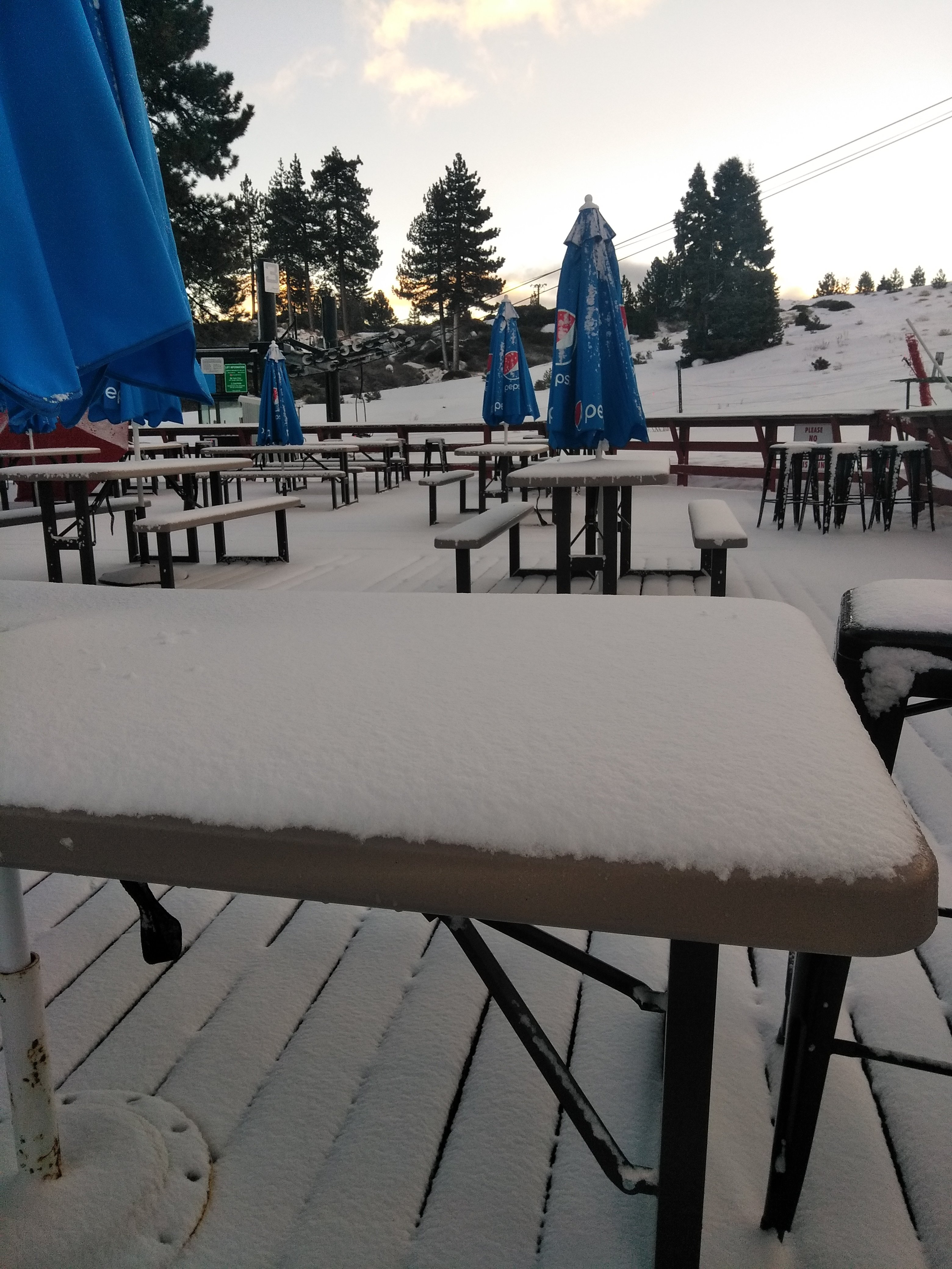 Snow Valley deck filled with tables covered in snow after a storm