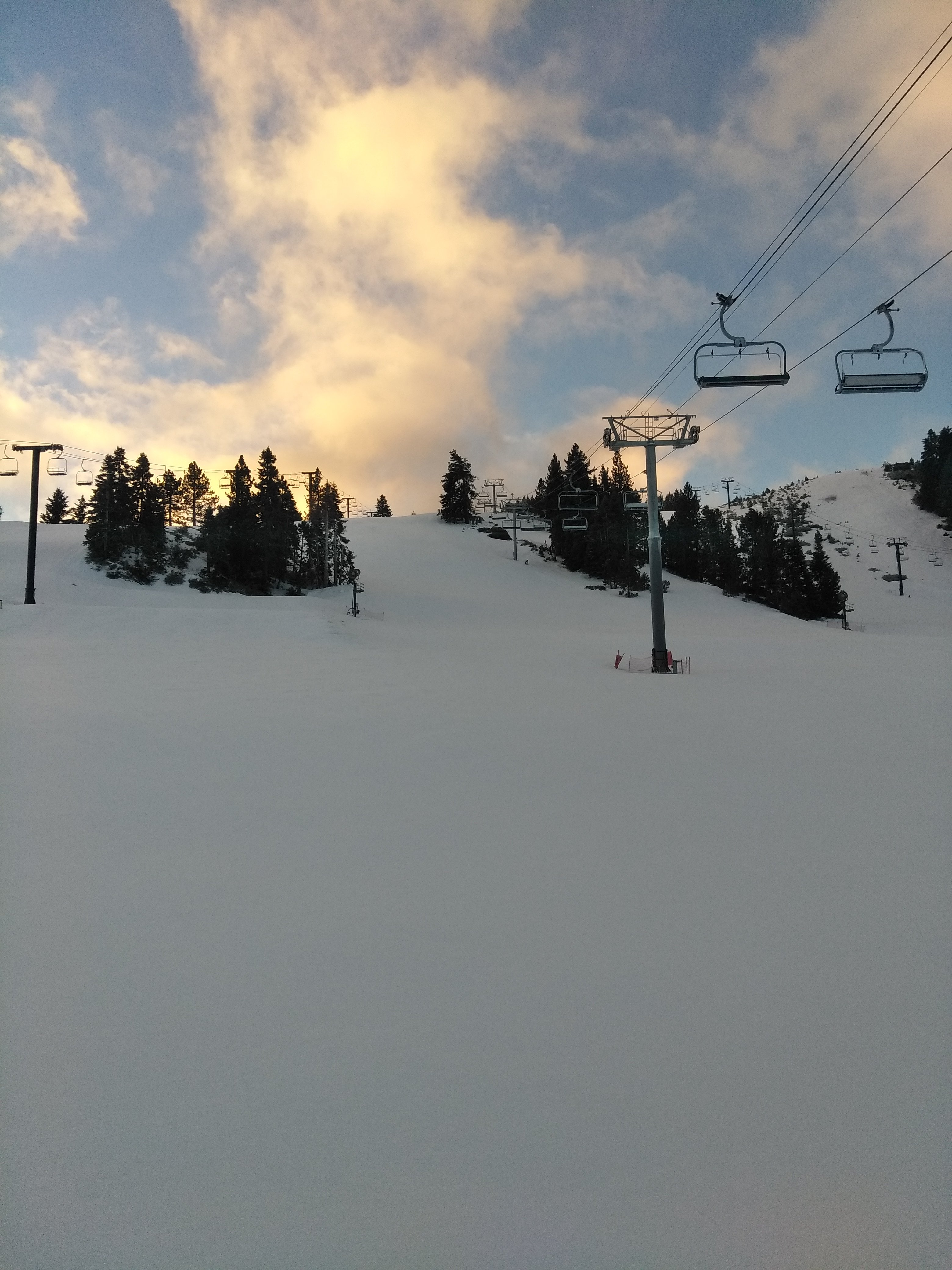 Scenery of ski lift and passing clouds overhead
