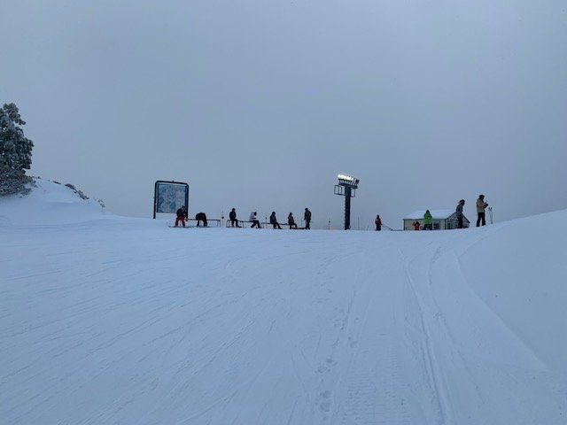 Snowboarders and skiiers taking break at top of mountain