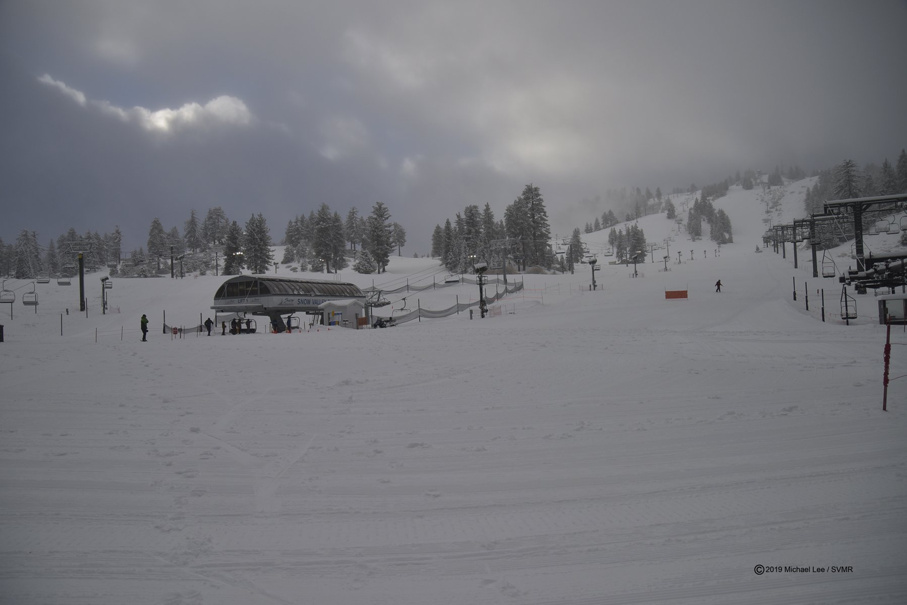 Landscape view of Snow Valley Express lift with clouds passing quickly overhead
