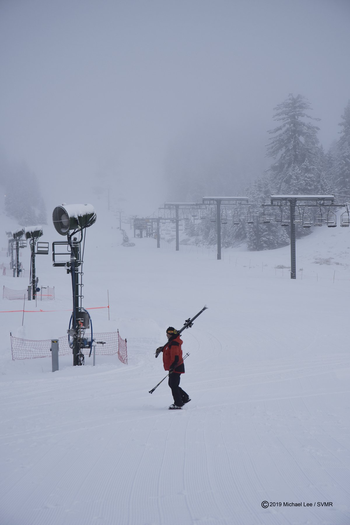 Man walks equipment between ski lift and snow making machines