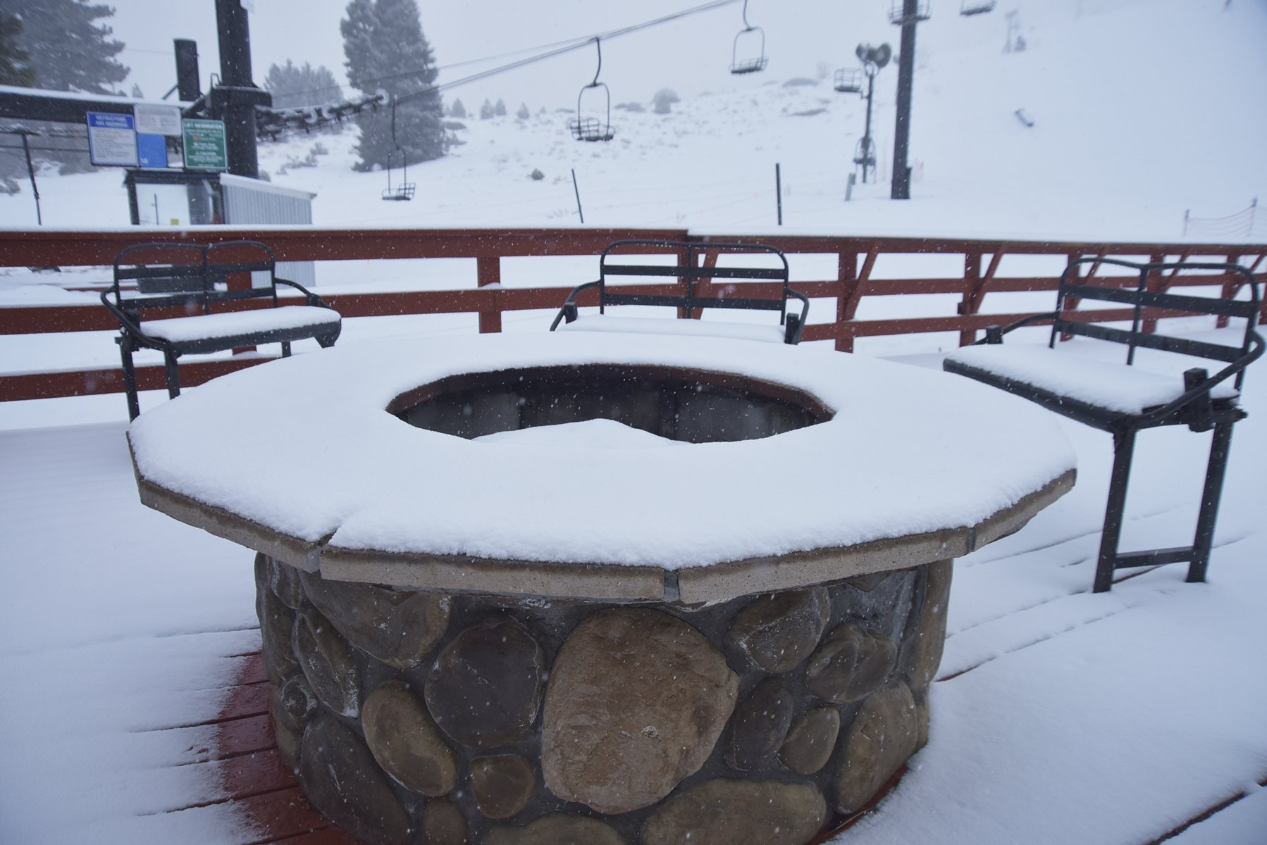 Fire pit on deck topped with snow while it is snowing
