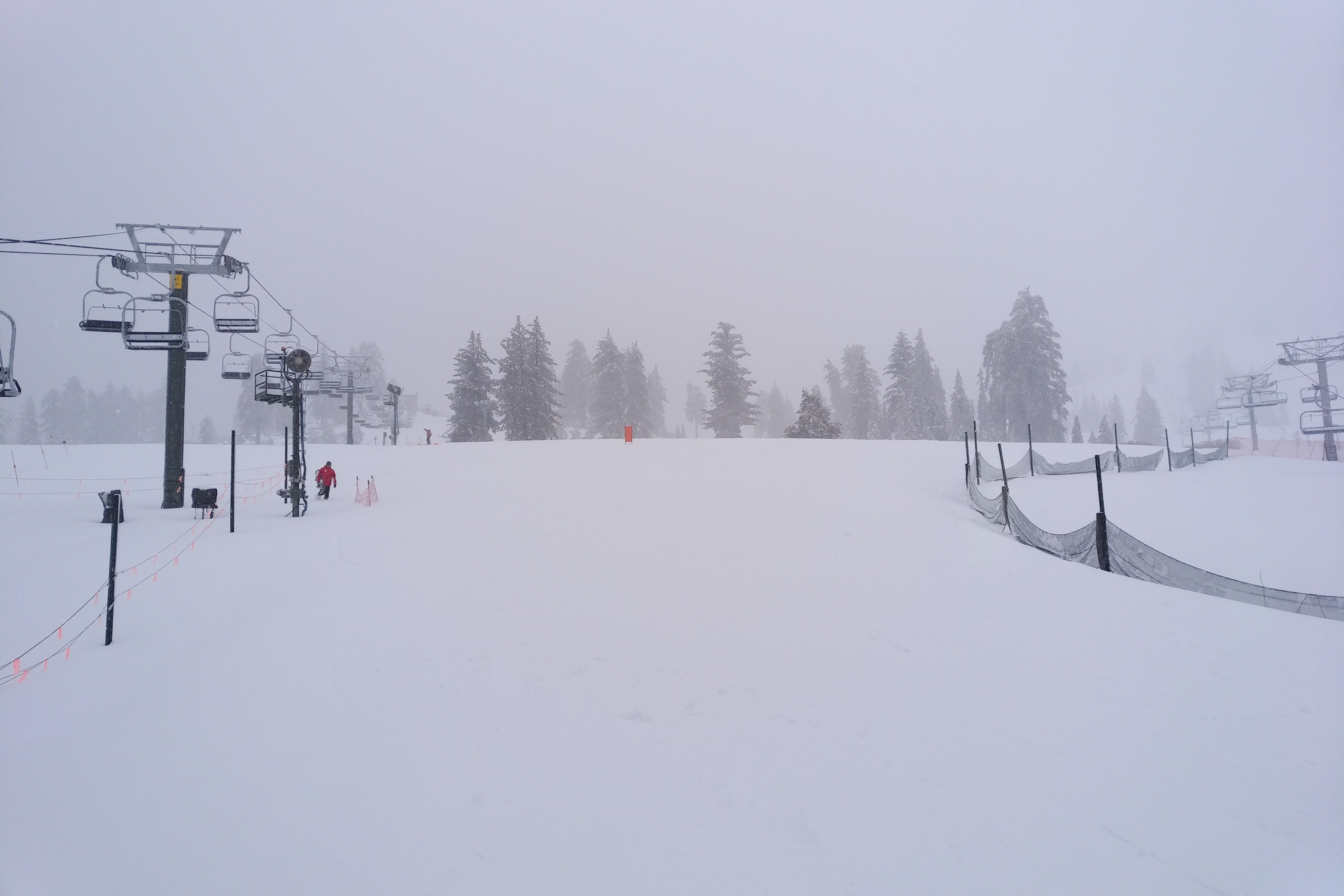 Ski lifts flank pristine snow in overcast weather