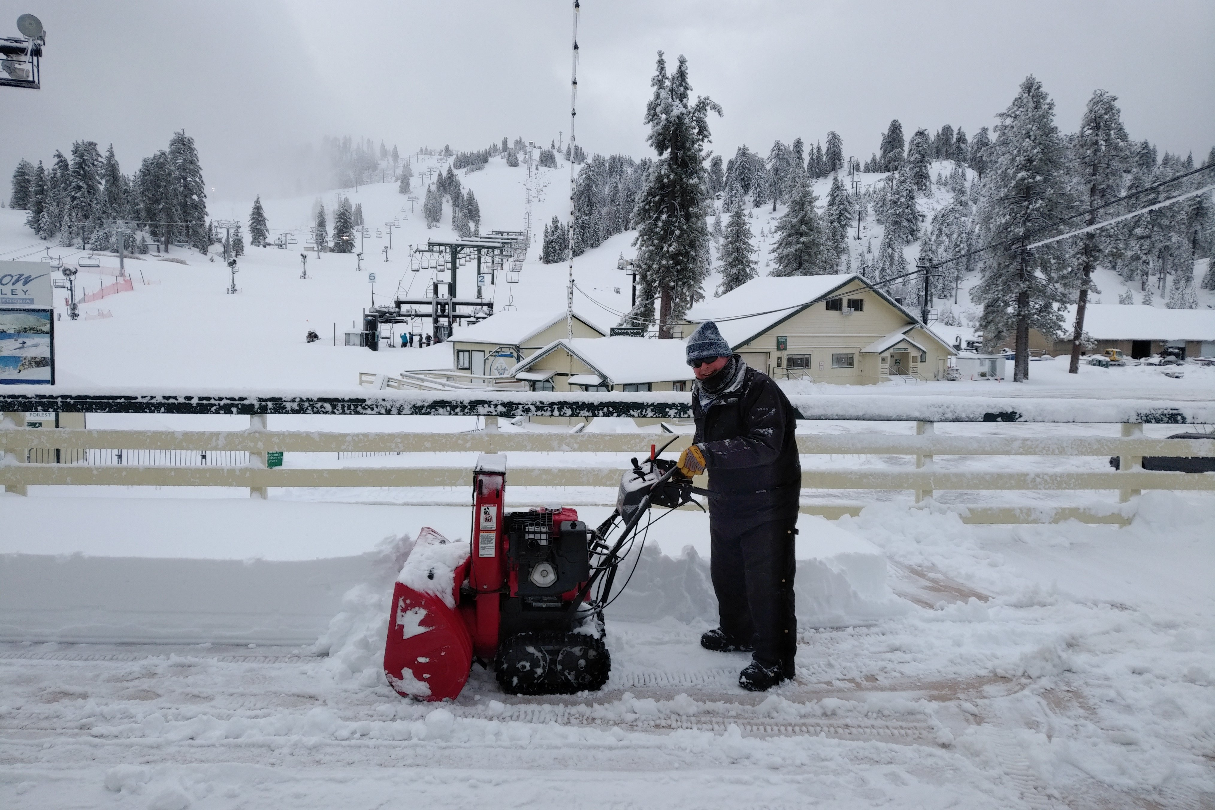 Smiling Snow Valley employee pushing snow blower over deck