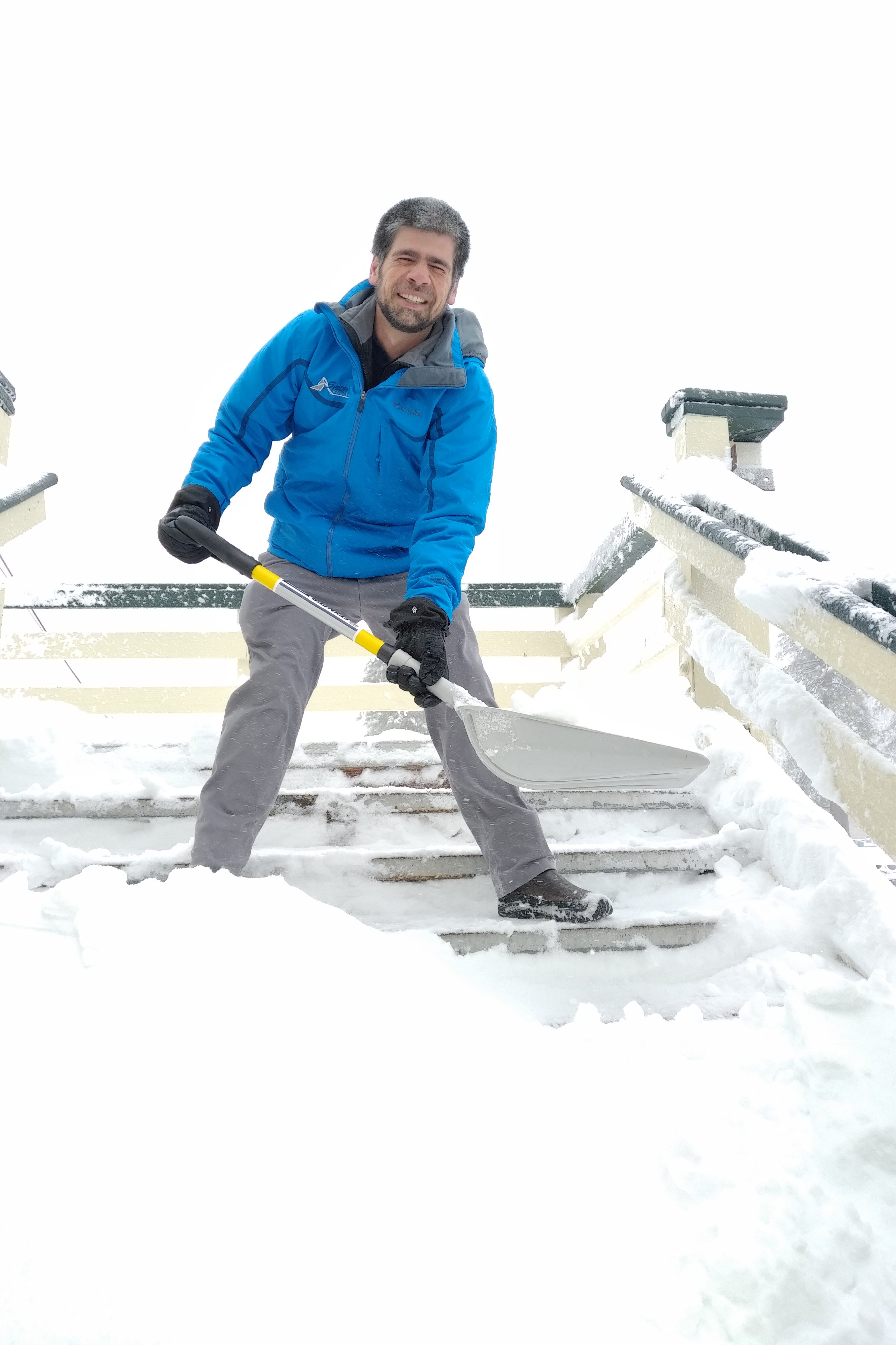 Snow Valley Vice President & General Manager smiling as he shovels stairs