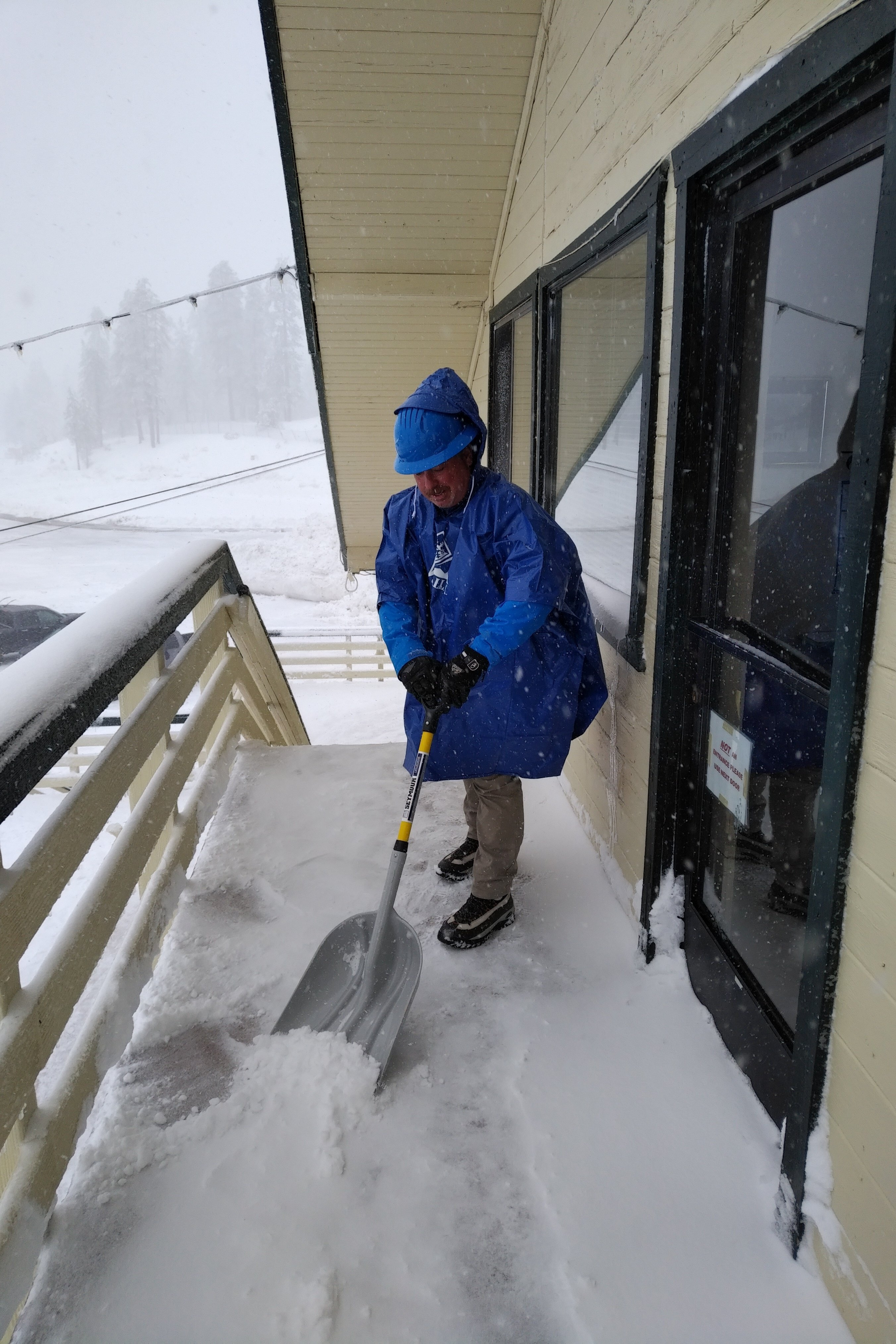 Snow Valley employee shoveling deck